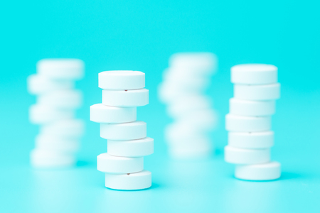 White pills or tablets stacked on each other in different positions on blue background Imagens
