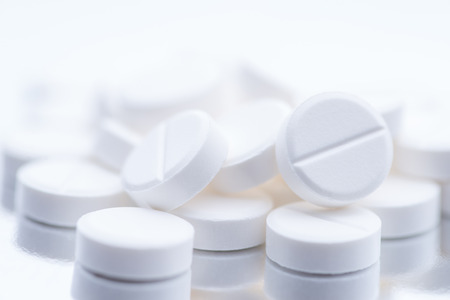 White pills or capsules on a white background with copy space.