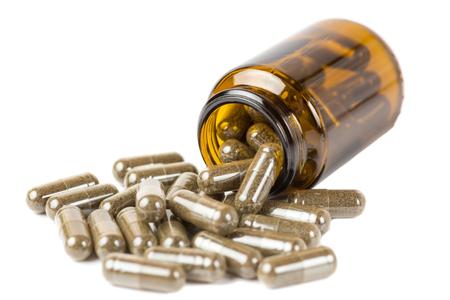 Aísle las píldoras o tabletas en el frasco de vidrio marrón sobre un fondo blanco. Aislar sobre un fondo blanco