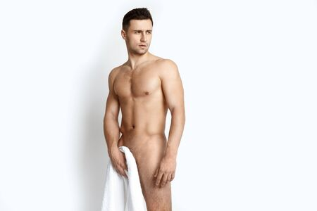 Strong stripped muscle male model with white towel on white isolated background