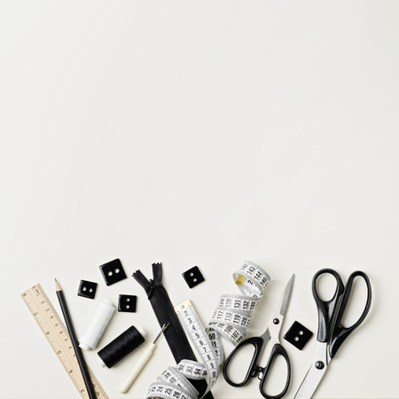 Everything for sewing in black and white. Fabric and thread, zipper and buttons, scissors and centimeter, pencil and ruler. Stock Photo