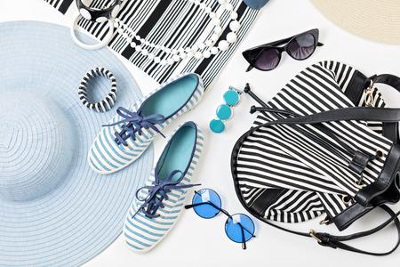 Mode-accessoires in zwart-wit en blauwe kleuren - hoed kleding, schoenen en tas, armbanden en glazen. Stockfoto