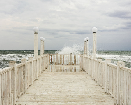 Pier with white wooden handrails at sea during a storm. Selective focus. Stock Photo
