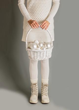 pies bonitos: ¡Feliz navidad y próspero año nuevo! La muchacha viste blanco sostiene una cesta de decoraciones de la Navidad.