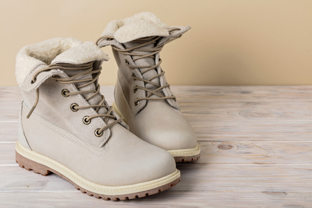 Bright leather winter boots on a light wooden background.