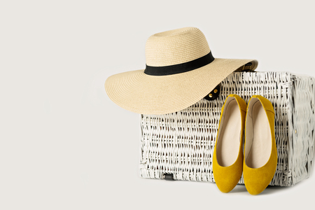 White wicker suitcase, a womans hat and yelow shoes. Stock Photo