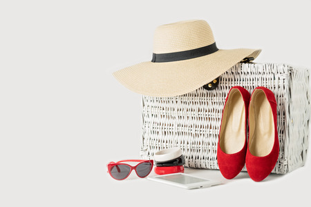 White wicker suitcase, womens hat, bracelets, sunglasses, e-book and red shoes
