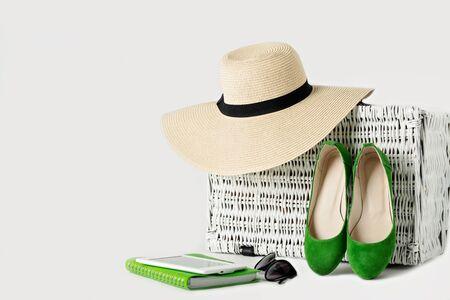 Witte rieten koffer, dameshoed, zonnebril, groene schoenen, e-book en notitieblok. Selectieve aandacht.
