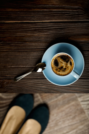 Cup of coffee on a wooden table and womens shoes. Selective focus.