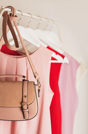 checkroom: Womens clothing in pink tones on a white hanger. Selective focus. Stock Photo