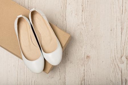 가벼운 나무 배경에 여성 신발 (발레 아파트) 화이트 색상. 선택적 포커스입니다. 스톡 콘텐츠
