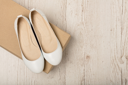 Women shoes (ballet flats) white color on a light wooden background. Selective focus.