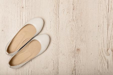 가벼운 나무 배경에 여성 신발 (발레 아파트) 화이트 색상. 선택적 포커스입니다.