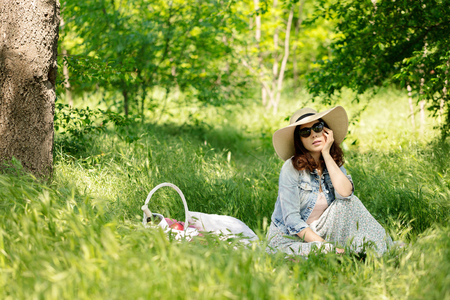 white wine: Summer time. Young woman in hat at a picnic in the forest. Selective focus. Stock Photo