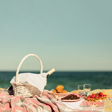 white wine: Summer time at the sea. Romantic picnic on the beach - wine, strawberries and sweets. Selective focus. Stock Photo