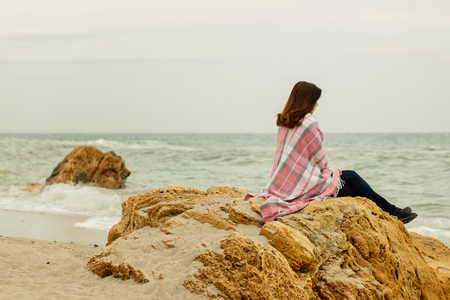 Young woman covered with a rug sits on the beach by the sea in cloudy weather. Selective focus. Reklamní fotografie