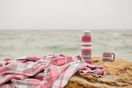 감 금 소 및 바다 근처 해변에 돌에는 보온병에서 핑크 격자 무늬. 선택적 포커스입니다.