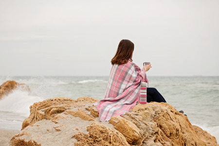 Young woman is covered with a rug sits on the seashore and drinking hot tea (coffee) from a thermos bottle. Selective focus. Reklamní fotografie