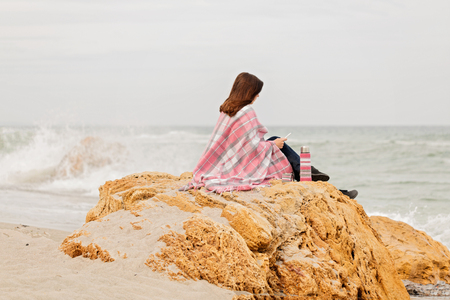 Young woman is covered with a rug sits on the seashore and reads an ebook. Selective focus. Stock Photo