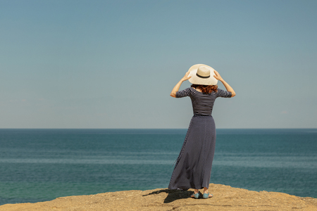 Young woman in a long dark blue skirt on the waterfront near the sea. Selective focus. Archivio Fotografico