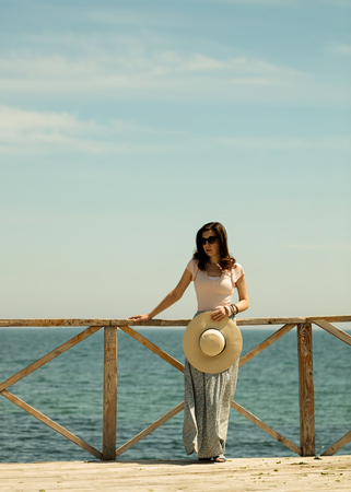 mujer mirando el horizonte: Young beautiful woman in a long skirt and hat stands on a wooden old pier on a background of a sea landscape. Selective focus. Foto de archivo