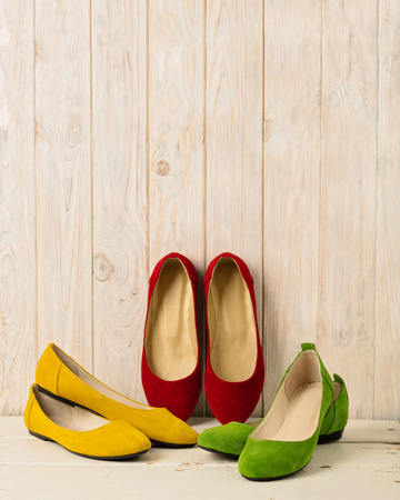 Red, green and yellow womens shoes (ballerinas) on wooden background. Selective focus. Stock Photo