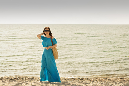 cerulean: Young beautiful woman on the beach in azure long dress with mobile phone in hand. Selective focus.