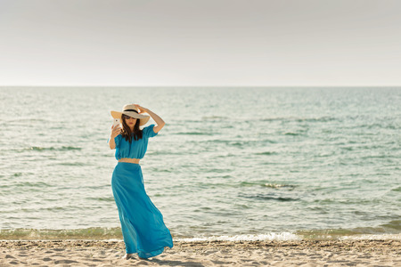 cerulean: Young beautiful woman on the beach in azure long dress takes pictures of herself on a smartphone. Selective focus.