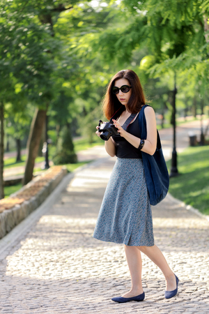 Young woman (photographer, tourist) in a blue skirt and black top holds a camera in her hand. Selective focus.