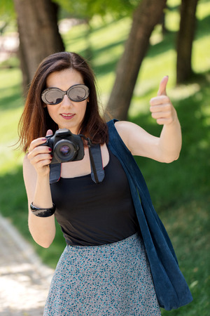Young woman (photographer, tourist) holds a camera and shows a thumb gesture (pollex, digitus primus). Selective focus.