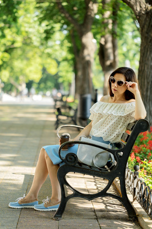 Young woman in park on bench drinking coffee. Selective focus.