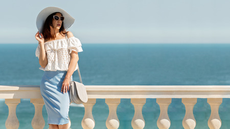 Young woman in a white blouse, blue pencil skirt and hat on a background of the sea horizon. Selective focus. Stock Photo