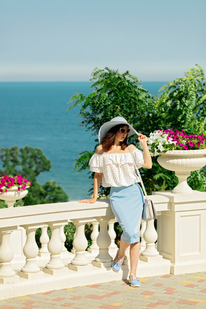 chic woman: Young woman in a white blouse, blue pencil skirt and hat on a background of the sea horizon. Selective focus. Stock Photo