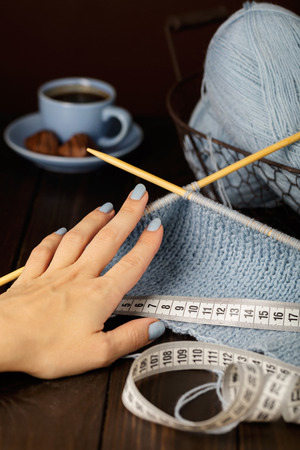 Knitting from light blue yarn. Female hand and centimeter.