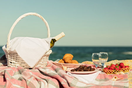 Summer time at the sea. Romantic picnic on the beach - wine, strawberries and sweets. Selective focus. Stock Photo
