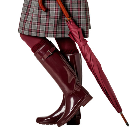 Female legs in a skirt in a cage, in burgundy pantyhose and in crimson rubber boots with an umbrella on an isolated background. Selective focus.