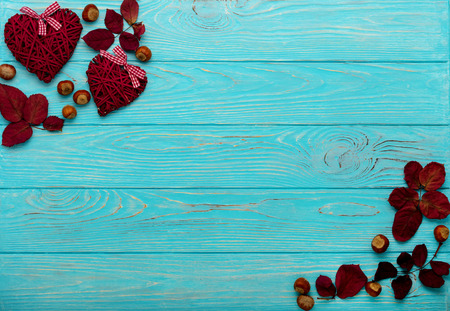 Flat lay frame of autumn crimson leaves, walnuts and decorative wicker hearts on a wooden background of azure color. Selective focus. Stock fotó
