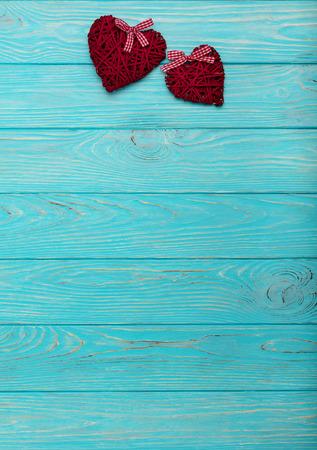 バレンタインの日。紺碧の木製の背景にバーガンディ色の装飾的な枝編み細工品の心。選択と集中。