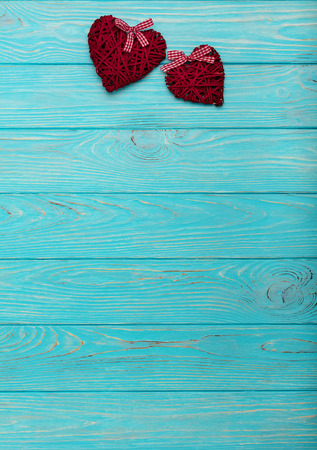 Valentines Day. Decorative wicker hearts of burgundy color on azure wood background. Selective focus.