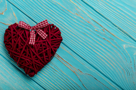 cerulean: Valentines Day. Decorative wicker hearts of burgundy color on azure wood background. Selective focus.