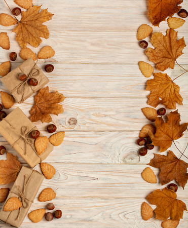 Flat lay frame of yellow leaves, cookies in the form of leaves, hazelnuts and gift boxes on a light wooden background. Selective focus. Stock Photo
