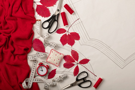 All for sewing - fabric, patterns and sewing accessories. Fashionable autumn colors. Trend of the season - colors Grenadine and Flame scarlet. Flat lay concept. Stock Photo
