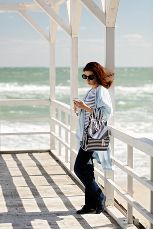 Young woman (brunette) in a light blue cardigan and navy jeans, with a striped backpack, walks along the beach, drinks coffee and looks into the phone. Selective focus.