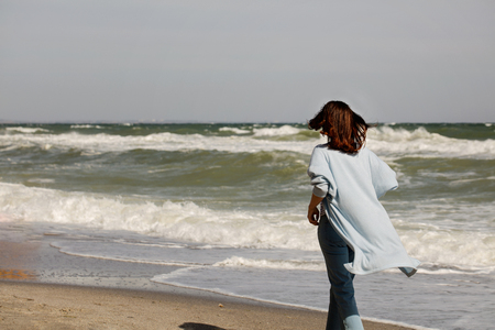 Young woman (brunette) in a light blue cardigan and jeans, with a backpack, walks along the beach. Selective focus. Stock Photo