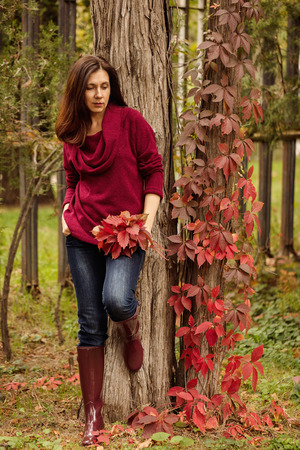 Young woman (brunette) in jeans, a sweater and crimson rubber boots is walking in an autumn park. Selective focus.