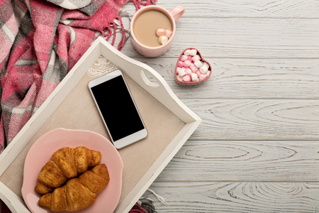 Knitted pillows and plaid, smartphone, croissants and coffee on a light wooden background. Top view. Flat lay.