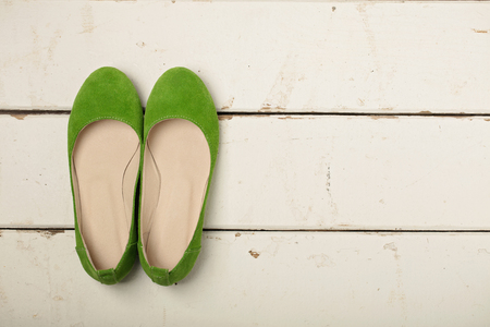 Green women's shoes (ballerinas) on wooden background. Selective focus.