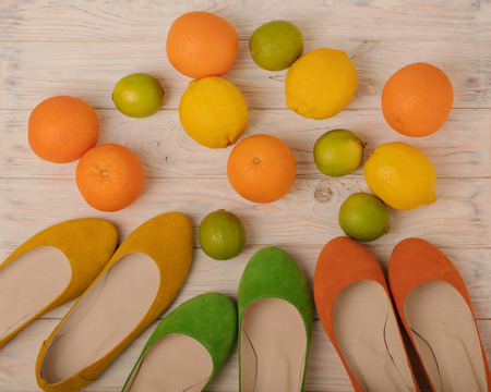 Summer conceptual photoset - women's shoes of yellow, orange and green colors and citrus - lemons, oranges and limes. Selective focus. Archivio Fotografico