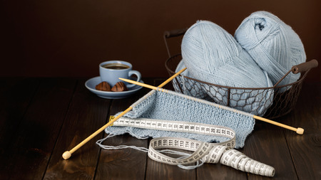 Knitting from light blue yarn. Cup of coffee and chocolates.