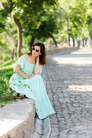 Young beautiful woman in a light green pastel long dress is sitting on a park bench. Selective focus. Фото со стока